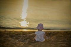 Une petite fille s'assied sur le sable par la mer et admire le coucher du soleil photo stock