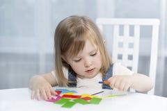 Une petite fille se rappelle des formes géométriques Verticale tôt d'éducation Image stock