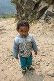 Une petite fille se tient sur une route de montagne le 28 mars 2018 dans le noeud Photographie stock