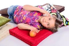 Une petite fille se trouvant à son téléphone de lit Image libre de droits