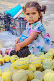 Une petite fille sombre s'assied sur le trottoir près des melons Image stock