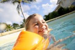 Une petite fille souriant et nageant Photo stock