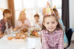 Une petite fille sourit et pose dans un chapeau de fête contre le contexte de sa famille, qui s'assied à une table de fête Images stock