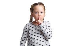 Une petite fille tient l'index près de la bouche, montrant un geste de silence D'isolement sur le fond blanc photographie stock