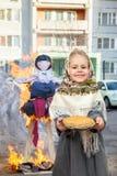 Une petite fille tient un plat des crêpes Photographie stock