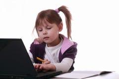 Une petite fille travaille avec un ordinateur portatif Photographie stock