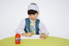 Une petite fille, un élève du cours préparatoire, apprenant à dessiner photos libres de droits