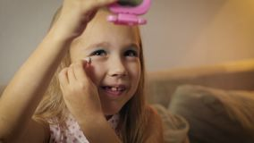 Une petite fille, un enfant fait un maquillage, peint des sourcils banque de vidéos