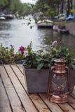 Une petite lanterne de cuivre est sur la table en bois avec des fleurs Images stock
