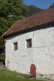 Une petite maison avec les murs blancs et les petites fenêtres et une porte à Bergen en Norvège Photo stock
