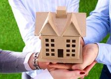 Une petite maison dans les mains Grands plans à l'avenir Image libre de droits