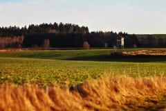 Une petite maison dans un domaine au coucher du soleil Photo stock