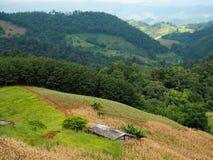 Une petite maison entourée par des montagnes Photographie stock
