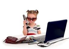 Une petite petite fille appelle le téléphone. Photo stock