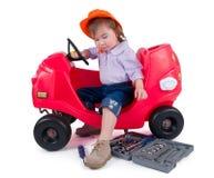 Une petite petite fille réparant le véhicule de jouet. Photos libres de droits