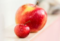 Une petite pomme de paradis sur un fond d'une grande pomme Maman avec un enfant Grand et petit, comparez, Photos libres de droits