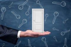 Une petite porte blanche se reposant sur une grande paume du ` s d'homme d'affaires avec beaucoup de clés dessinée sur un fond de Photo libre de droits
