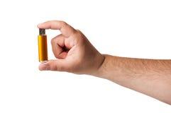 Une petite prise de bâton de mémoire d'usb par des doigts sur un fond blanc Images libres de droits