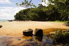 Une petite rivière avec le fond arénacé jaune et brun coulant dans la mer d'Andaman près de la forêt verte, Khao Lak, Thaïlande Image stock