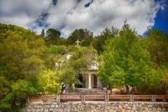 Une petite vieille église cachée parmi les arbres d'un verger olive Photos stock