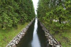 Une petite voie d'eau avec des arbres coniféres et un pont Images stock