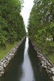 Une petite voie d'eau avec des arbres coniféres et un pont Photographie stock