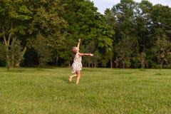 Une photo chaude d'une petite fille courant le pied nu sur une herbe verte Image libre de droits