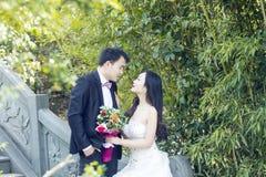 Une photo chinoise de mariage du ` s de couples qui se tiennent sur un pont antique en pierre en parc de la BO de shui à Changhaï Images libres de droits