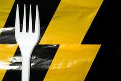 Une photo conceptuelle au sujet des dangers des ustensiles en plastique, d'une fourchette et d'une bande protectrice image stock