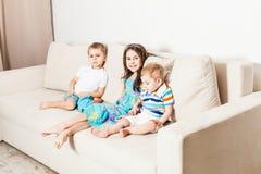 Une photo d'une belle petite fille ses deux frères s'asseyant sur le sofa photo stock