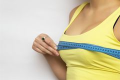 Une photo d'une femme heureuse de jeune ajustement vérifiant sa mesure de sein au-dessus du fond blanc photo stock