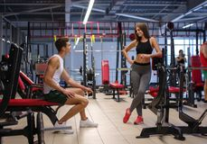 Une photo d'une formation personnelle flirtant avec une jeune dame sportive sur un fond de gymnase Concept sain de style de vie images stock