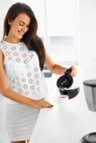Une photo d'un café se renversant de femme dans une tasse blanche Photographie stock libre de droits