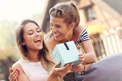 Une photo de deux amie faisant un cadeau d'anniversaire de surprise Images stock