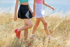 Une photo de deux femmes élégantes portant les vêtements colorés dans l'extérieur Jambes renversantes des filles sur un fond natu Photo stock