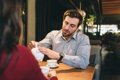 Une photo de type se reposant à la table avec son amie et versant du thé dans la tasse pour eux Il écoute Photographie stock libre de droits