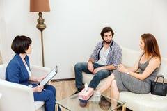 Une photo des couples se reposant ensemble sur le sofa et regardant entre eux très sérieusement Le docteur les regarde et Image stock