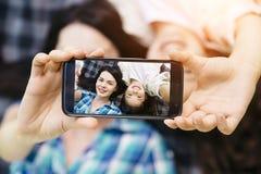 Une photo des filles se trouvant sur la couverture et tenant le téléphone ensemble Il est noir Le petit gisl sourit Photographie stock libre de droits