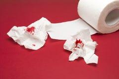 Une photo des merdes utilisées du papier hygiénique ensanglanté et un papier hygiénique roulent sur le fond rouge Baisses de sang Images stock