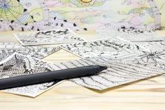 Une photo des modèles abstraits de griffonnage faits en stylo noir de revêtement sur la table en bois Courses de stylo Griffonnag Photo libre de droits