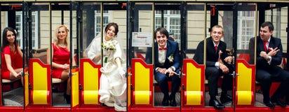 Une photo des nouveaux mariés de sourire s'asseyant avec des amis dans les portes Images libres de droits