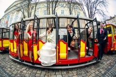 Une photo des nouveaux mariés et des amis s'asseyant dans les portes de t rouge Image libre de droits