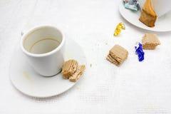 Une photo des tasses sales, du sachet à thé utilisé, de l'emballage de bonbons au chocolat et du chocolat sec waffles des restes  images stock