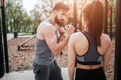 Une photo du jeune homme et de la femme exerçant l'ouside en parc Il montre comment faire la boxe d'une bonne manière Elle est Image libre de droits