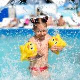 Une photo ensoleillée d'une petite fille de sourire appréciant jouer et nager dans la piscine ouverte Images libres de droits