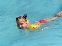 Une photo ensoleillée d'une petite fille de sourire appréciant jouer et nager dans la piscine ouverte Photo libre de droits