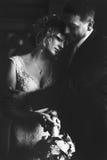Une photo noire et blanche d'un marié étreignant une jeune mariée réfléchie image libre de droits