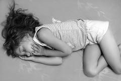 Une photo noire et blanche d'une petite fille dormant dans un lit Images stock