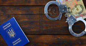 Une photographie d'un passeport étranger ukrainien, d'un argent ukrainien et de menottes de police Concept d'earnin illégal photographie stock