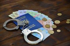 Une photographie d'un passeport étranger ukrainien, d'un argent ukrainien et de menottes de police Concept d'earnin illégal photos libres de droits